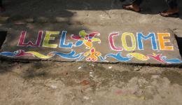 Vor dem, beim letzten Aufenthalt neu eröffneten Nähzentrum, empfängt uns ein buntes Rangoli (aus Farbpulver gestreut).