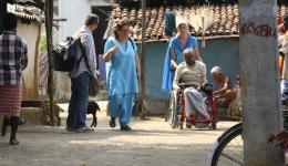 Alexandra fährt einen alten Mann mit einem im Juli gekauften Rollstuhl durch die Brajraj-Kolonie.