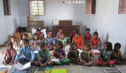 Chakia colony: In India a normal class room. Students sitting on the ground, holding their notebooks on their legs.