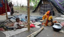 Mother with child in front of her hut.