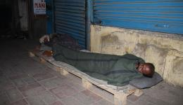 """In order to """"escape"""" the worst ground cold, this man has made himself a night camp on a pallet."""