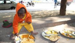 Suppenküche. Der kleine Junge auf dem Foto isst den großen Teller alleine leer.