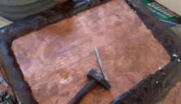 With hammer and nail the copper plates are engraved.