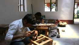 The young men are processing the copper items with enthusiasm and great diligence.