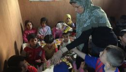Visiting refugee camps in Lebanon. Alexandra in customary Lebanese clothing distributing school material.
