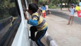 Distributing from the window of a 16-seat bus. The boy jumps up the bus, where Michael hands out the biscuits.
