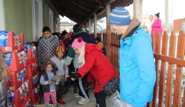 Each child receives a cap and a pack of biscuits. Emma shows the little ones where they are to go. The adults and the village chief help to have the distribution run smoothly.