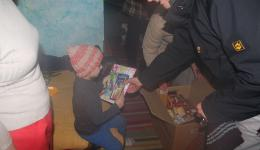 The family is very happy about the package. Frank gives the little boy the coloring book and pencils. His brother is sitting on the bed, the small room is bedroom and living room in one.
