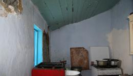 The kitchen, which is attached outside the house. There is a gas stove and a few pots