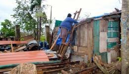 Eine Frau versucht, zwischen den täglichen Regenfällen,  notdürftig ihr Haus zu reparieren...