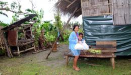 Eine Mutter mit ihrem Kind freut sich sehr über die Päckchen voll mit Reis und Nudeln...