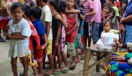 Viele, viele Kinder stehen Schlange für Brötchen, Biskuits und Bonbons...