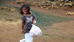 Voller Freude läuft das Mädchen mit der Tüte voll Nudeln, Bisciuts und Seifen zu seiner Mutter...