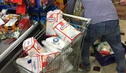 In supermarkets several carts are filled with packages.