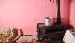 """A young widow lives here with nine children. Her husband died a year ago. The stove in one corner of the room which is also used for cooking will hardly sufficiently warm the uninsulated """"ruin"""" of the house when temperatures will be as low as -20°C."""