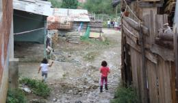Arrival in a settlement on the outskirts. The houses are located on a slope. During the night it had been raining heavily and only part of the way between the houses is fixed.