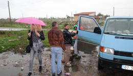 It rains heavily and all help to bring the goods as dry as possible into the building (in front with umbrella: Vjosa).