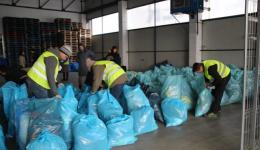 Bruno, Fenja and Matthias are knotting the bags before they are loaded into the small truck.
