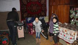 The stove has not yet been installed. The children feel cold and step from one foot on the other.