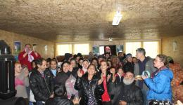 The small church is fully occupied and the rest of the people have to remain outside. Before potatoes and clothing are distributed all are rejoicing and singing songs.