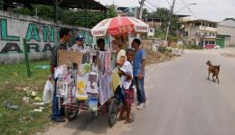 A street vendor is supported by buying and giving away her products...