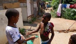 """""""Von Kind zu Kind"""" …- Miguel, der Sohn von José darf Kekse und Süßigkeiten an alle Kinder auf der Müllhalde verteilen..."""
