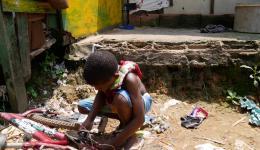 Ein Junge repariert ein Fahrrad, das er zwischen dem Müll gefunden hat. Auch die Teile hat er sich zusammengesucht.