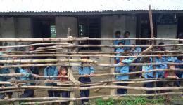Durch den Zaun der einfachen Schule blicken die Kinder neugierig auf die Besucher.