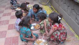 An verschiedenen Stellen wird an die Straßenkinder in Delhi Essen verteilt