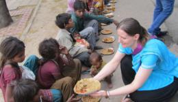 """Katja überreicht den Kindern """"Stuffed Parantha"""" (indischen Kartoffelpfannkuchen)"""