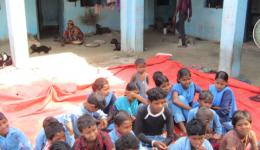 The school children have gathered on a tarp in the courtyard.