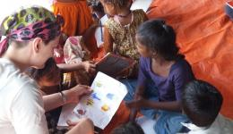 On a tarpaulin all sit together and the children show Katrin and Ludmila their notebooks.