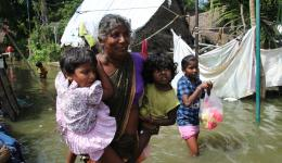 Because of poisonous animals, water snakes etc. this woman is carrying her children through the muddy not transparent water.