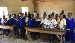 Schulkinder in ihrem Klassenzimmer in der Nähe von Iringa, Holz zum Bau von Schulbänken ist genügend da, die Dorfbewohner haben daher die Möbel gemeinsam angefertigt, ansonsten fehlte alles!!