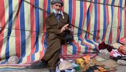 Muhamad ist 82 Jahre alt. Am Straßenrand verkauft er Kleinigkeiten, die ihm jemand gegeben hat. Die kleine Rente wurde ihm vor 5 Jahren gestrichen. Warum weiß er nicht.