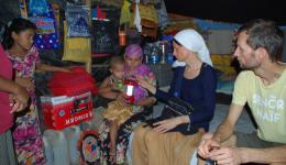 In one of the camp huts. The mother shows one of the distributed solar lamps.