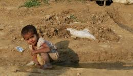 A little girl playing in the gutter besides the hut of her family.