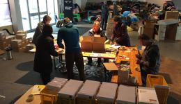 """Behind the """"packing isle"""" the completed letters are piled up in transportation boxes. In one common exertion the whole mailing material gets packed on one single forenoon. Many thanks to All!"""
