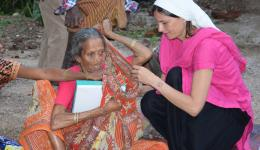 Alexandra helps the woman to stow her things into her sari since she has no more fingers.