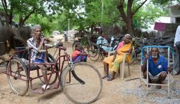 Geduldig sitzen die Menschen und beobachten die Gespräche über den Weiterbau des hochgelegenen Wassertanks.