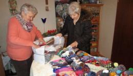 Frau Nüsslein mit ihrer Cousine Frau Nüsslein beim Zusammenpacken der übers Jahr gestrickten Mützen.
